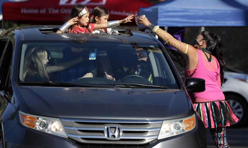 Jennifer Olivas hands treats to 6-year-old twins Loucia Ramirez, left, and Adriana Ramirez in Monterey Park.