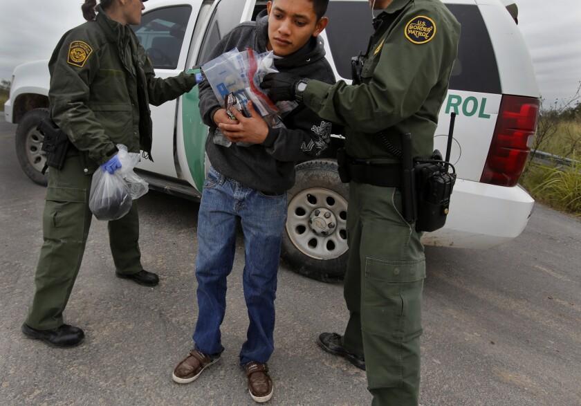 Border Patrol agents apprehend an immigrant along the Mexico border near McAllen, Texas, in 2014.