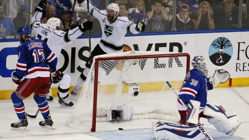 Kings forward Jeff Carter, top center, celebrates with teammate Dwight King after scoring on New York Rangers goalie Henrik Lundqvist with less than a second left in the first period of the Kings' 3-0 win in Game 3 of the Stanley Cup Final on Monday.