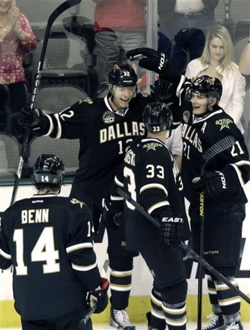 Dallas Stars right wing Alex Chiasson (12) celebrates his goal with teammates Alex Goligoski (33), Loui Eriksson (21) and Jamie Benn (14) during the first period of an NHL hockey game against the San Jose Sharks, Saturday, April 13, 2013, in Dallas. (AP Photo/LM Otero)