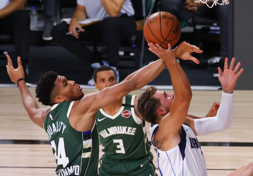 The Milwaukee Bucks' Giannis Antetokounmpo blocks a shot by the Dallas Mavericks' Luka Doncic.