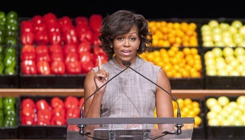 FILE - In this Jan. 20, 2011 file photo, first lady Michelle Obama takes part in Wal-Mart's announcement of a comprehensive effort to provide healthier and more affordable food choices to their customers, in Washington. Recent changes put in place by the food industry are in response to the campaig