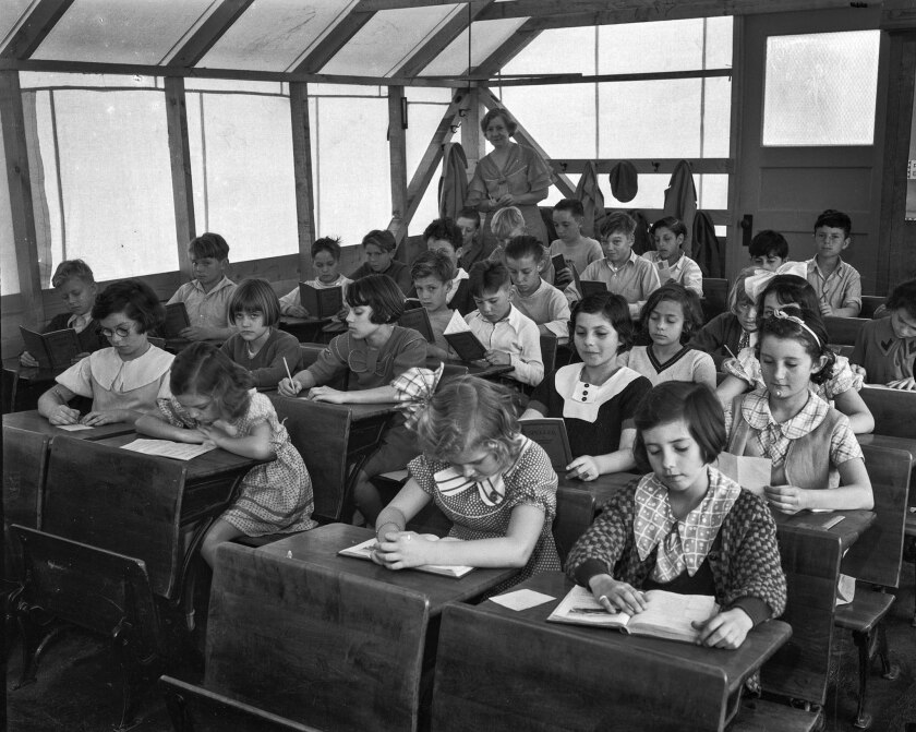 March 1934: Schoolchildren diligently read while their teacher watches from the back of their makesh