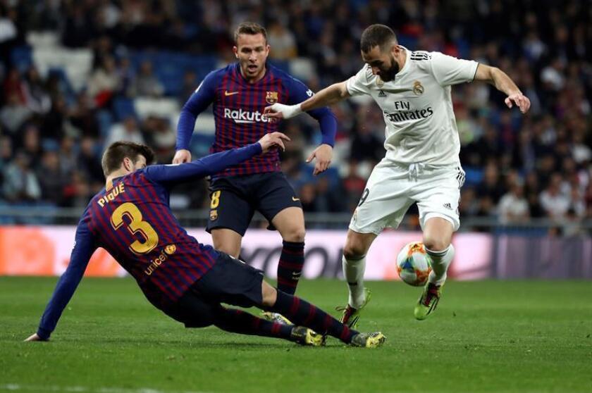 El delantero francés del Real Madrid, Karin Benzema (d), intenta llevarse el balón ante el defensa del FC Barcelona, Gerard Piqué, durante el encuentro correspondiente a la vuelta de las semifinales de la Copa del Rey que disputaron en el estadio Santiago Bernabéu, en Madrid. EFE