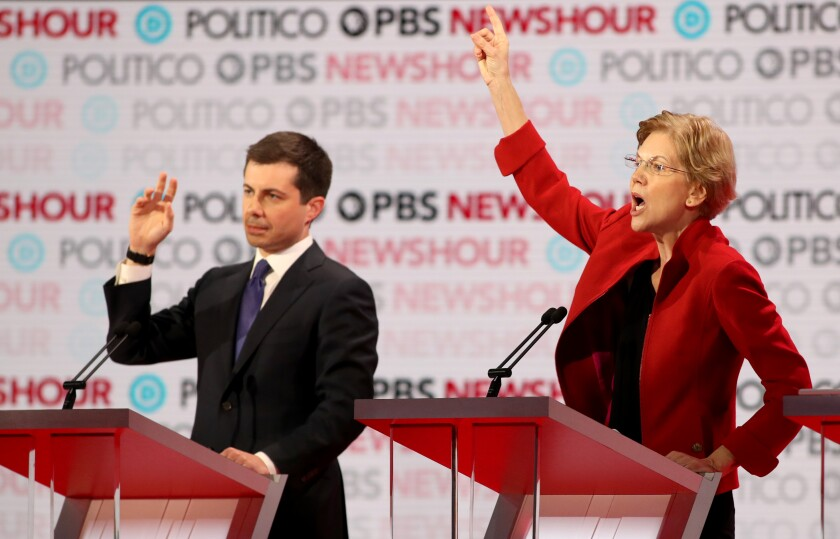 Candidates Pete Buttigieg and Elizabeth Warren raise their hands at Thursday's Democratic presidential primary debate in Los Angeles.