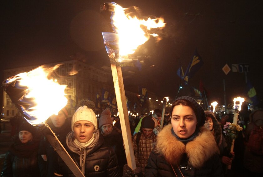 Ukrainian nationalists carry torches during a rally in downtown Kiev, Ukraine, late Wednesday, Jan. 1, 2014. The rally was organized on the occasion of the birth anniversary of Stepan Bandera, founder of a rebel army that fought against the Soviet regime and who was assassinated in Germany in 1959.