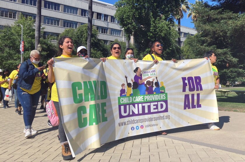 """People wearing yellow T-shirts hold a banner reading """"Child  care for all."""""""