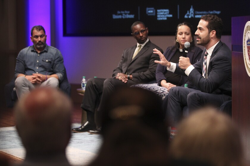 """Joshua Sayles speaks while stage with fellow panelists, from left, Pardeep Singh Kaleka, the Rev. Kylon Middleton, and the Rev. Tracy Howe Wispelwey, during the """"A Path Forward"""" event at University of San Diego on Wednesday."""