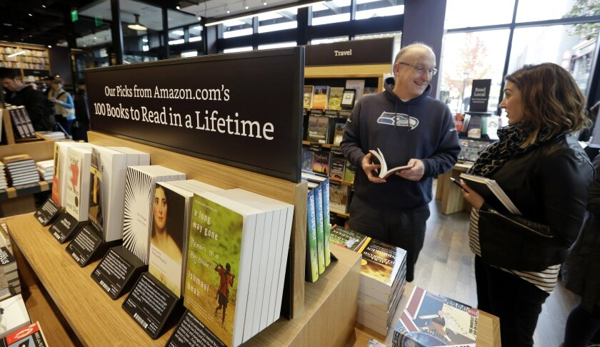 Customer Jeff Edward, left, talks with Amazon employee Sarah Gelman as Edward shops at the opening day for Amazon Books, the first brick-and-mortar retail store for online retail giant Amazon, Tuesday, Nov. 3, 2015, in Seattle. The company says the Seattle store, coming two decades after it began s