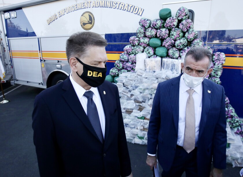 DEA's Timothy J. Shea and Bill Bodner stand next to a huge haul of meth, cocaine, heroin at the DEA warehouse.