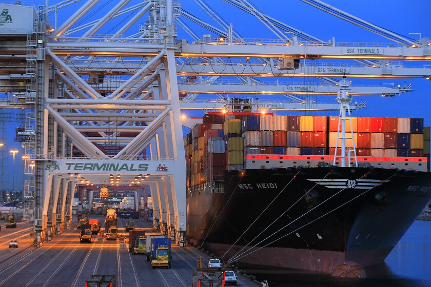 Cranes take cargo containers from a ship docked in the Port of Los Angeles in April.