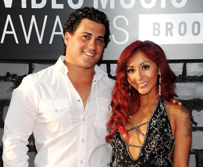 """FILE - In this Aug. 25, 2013 file photo, Nicole """"Snooki"""" Polizzi, right, and Jionni LaValle arrive at the MTV Video Music Awards in the Brooklyn borough of New York. Snooki has officially tied the knot. Former """"Jersey Shore"""" star Polizzi married boyfriend LaValle in a church ceremony Saturday, Nov. 29, 2014, in East Hanover, about 15 miles west of New York City. (Photo by Evan Agostini/Invision/AP, File)"""
