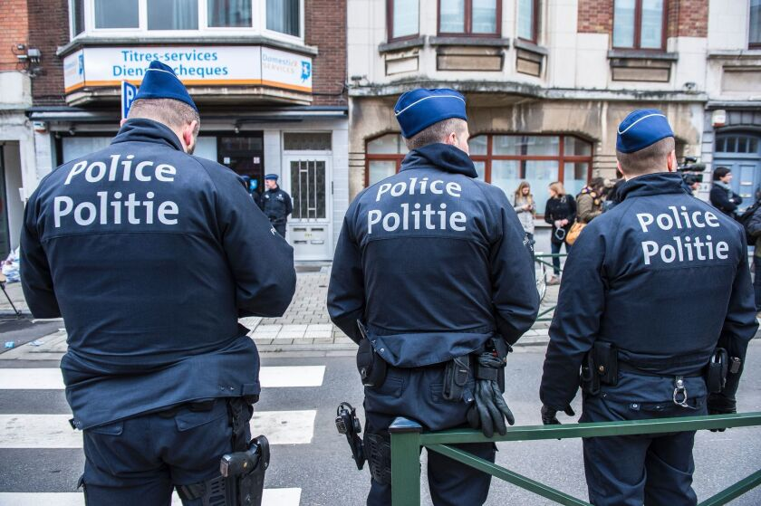 Police officers stand guard in the Schaerbeek district in Brussels during an anti-terrorism operation on March 25.