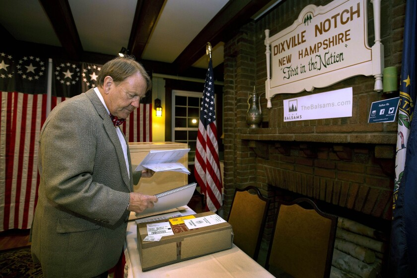 FILE - In this Nov. 7, 2016, file photo, Town moderator Tom Tillotson arrives with ballots as voters get ready to cast their votes just after midnight in Dixville Notch, N.H. Tom's father Neil Tillotson, who bought the resort called the Balsams, arranged for early voting at the hotel beginning in 1960. But the tiny, isolated community near the Canadian border may need to forfeit that tradition in 2020. The attorney general's office said the community is currently missing a required official in order to hold an election in the Feb. 11 primary. (AP Photo/Jim Cole, File)