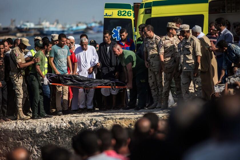La Guardia Costera de Egipto y rescatistas trasladan en una camilla el cadáver de un pasajero de un barco que naufragó frente a la costa de Egipto en el Mar Mediterráneo, en Rosetta, Egipto, el jueves 22 de septiembre de 2016. (AP Foto/Eman Helal)