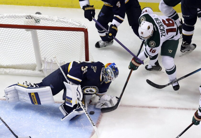 St. Louis Blues goalie Jake Allen, left, stops a shot from Minnesota Wild's Jason Zucker (16) during the second period of an NHL hockey game Saturday, Oct. 31, 2015, in St. Louis. (AP Photo/Jeff Roberson)