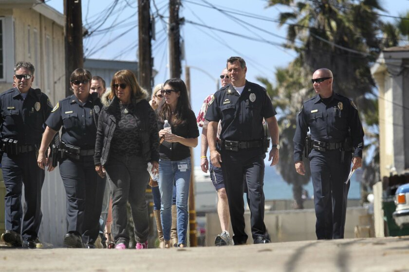 San Diego Police Captain Andy Mills, second from right, and members of the police department that work in Ocean Beach and members of the Mainstreet association and Town Council toured some of the alleys and streets as part of their walk around the Ocean Beach.