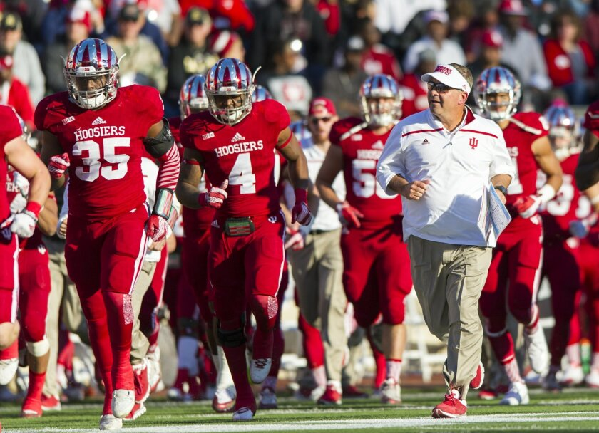 FILE - In this Oct. 17, 2015, file photo, Indiana head coach Kevin Wilson, right, runs off the field with the team as they head to the locker room after the first half of an NCAA college football game against Rutgers, in Bloomington, Ind. Indiana takes on Maryland on Saturday in College Park, Md. (AP Photo/Doug McSchooler, File)