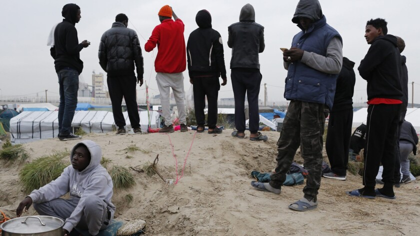 """Migrants on the grounds of """"the Jungle,"""" a camp in Calais."""