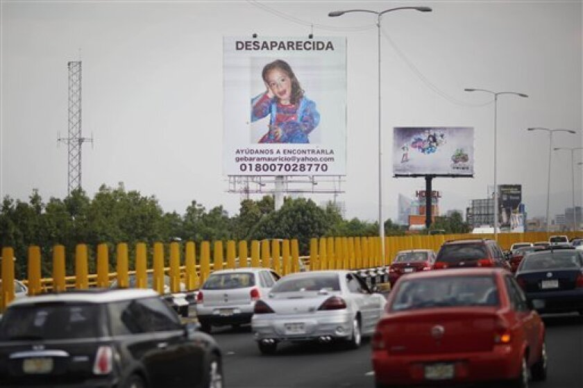 "Vehicles pass a billboard of Paulette Gebara Farah with the words in Spanish ""Disappeared, help us find her"" in Mexico City, Wednesday, March 31, 2010. The body of Farah, a disabled 4-year-old girl, was found Wednesday in her own bedroom, 10 days after her wealthy parents reported her missing and stirred nationwide sympathy with a public campaign to find her. (AP Photo/Alexandre Meneghini)"
