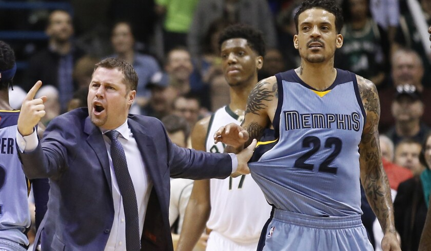 Grizzlies Coach David Joerger holds back Matt Barnes (22) after a double technical was called on Barnes and Milwaukee's John Henson late in a game Thursday.