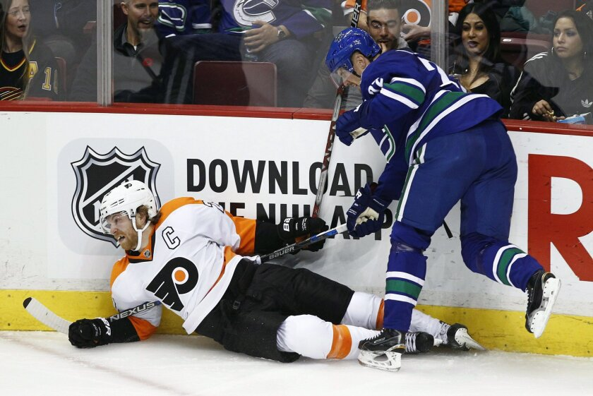 Vancouver Canucks' Daniel Sedin (22) checks Philadelphia Flyers' Claude Giroux (28) during the second period of an NHL hockey game in Vancouver, British Columbia, Monday, Nov. 2, 2015. (Ben Nelms/The Canadian Press via AP) MANDATORY CREDIT