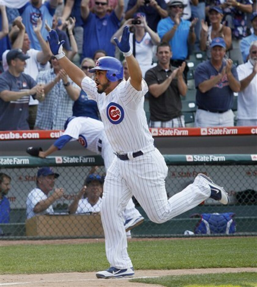 Chicago Cubs pinch-hitter Geovany Soto heads home, celebrating his three-run home run off San Francisco Giants relief pitcher Ramon Ramirez, scoring Starlin Castro and Darwin Barney, during the 13th inning of a baseball game Thursday, June 30, 2011, in Chicago. The Cubs won 5-2. (AP Photo/Charles R