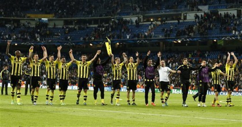 Dortmund players celebrate advancing to the final after the Champions League semifinal second leg soccer match between Real Madrid and Borussia Dortmund at the Santiago Bernabeu stadium in Madrid, Spain, Tuesday, April 30, 2013. (AP Photo/Andres Kudacki)