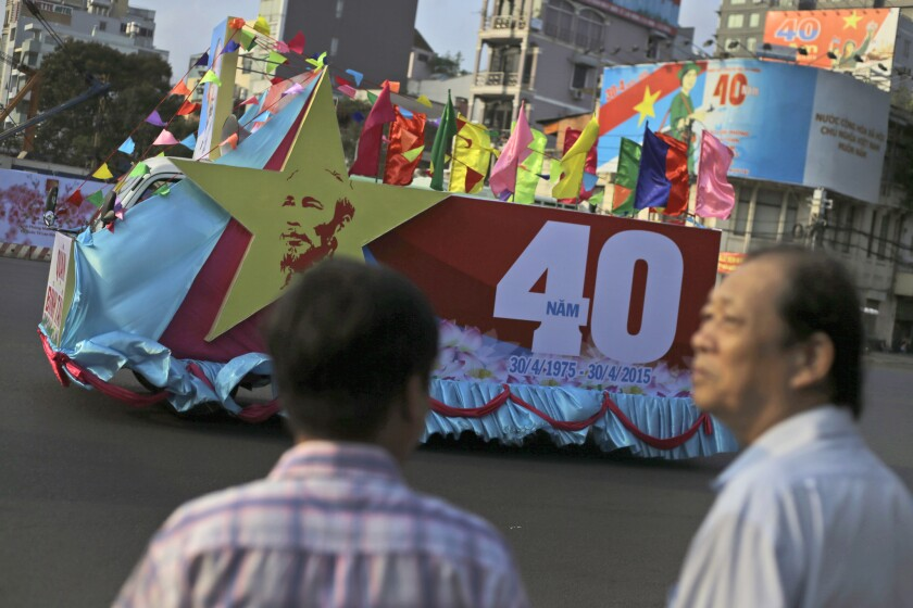 Vietnamese men watch as a float drives past by during a parade ahead of the celebration of the 40th anniversary of the end of the Vietnam War in Ho Chi Minh City, formerly known as Saigon, on April 29.