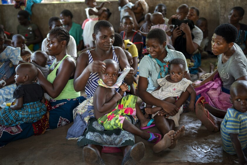FILE - In this Wednesday, Dec. 11, 2019 file photo, residents of the Malawi village of Tomali wait to have their young children become test subjects for the world's first vaccine against malaria in a pilot program. The world's first malaria vaccine should be given to children across Africa, the World Health Organization recommended Wednesday Oct. 6, 2021, a move that officials hope will spur stalled efforts to curb the spread of the parasitic disease. (AP Photo/Jerome Delay, file)