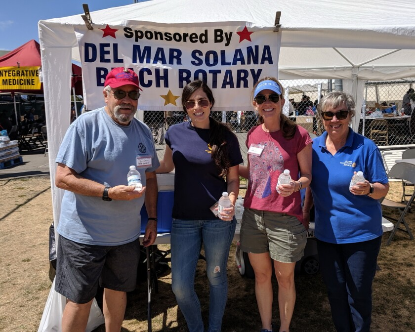 Del Mar-Solana Beach Past President and Marine Bill Sutton (left), organized and led 25 other Rotarians and friends in handing out chilled water bottles and encouragement at the recent three-day Stand Down San Diego 2019 program for homeless vets and their dependents. Rotarians Radia Hunter, Molly Fleming, and Suzanne Sutton joined Sutton to hand out water on the early Friday morning shift.