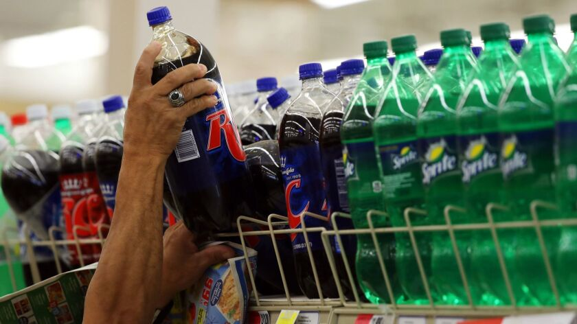 A shopper grabs a two-litre bottle of soda on Wednesday, Oct. 11, in Chicago.