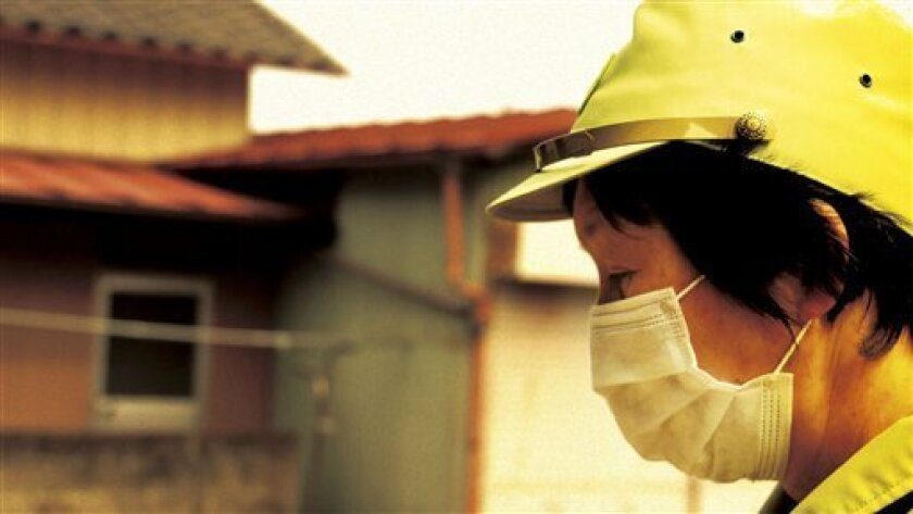 "In this image made from a scene from the film ""Fukushima: Memories of the Lost Landscape"" released by Yojyu Matsubayashi, Kyoko Tanaka, a city council member of Minami Soma, patrols in the deserted town after evacuation of the residents, on April 3, 2011. Japanese film director Matsubayashi took a"