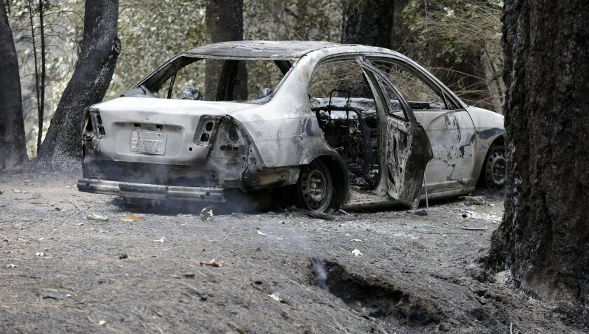 The charred remains of a car belonging to Leonard Neft, who has been missing since a wildfire tore through the area and destroyed his home days earlier, sits in the Anderson Springs area Wednesday, Sept. 16, 2015, near Middletown, Calif. Aided by drought, the flames have consumed more than 109 square since the fire sped Saturday through rural Lake County, less than 100 miles north of San Francisco. Cooler weather helped crews gain ground and the fire was 30 percent contained Wednesday. (AP Photo/Elaine Thompson)