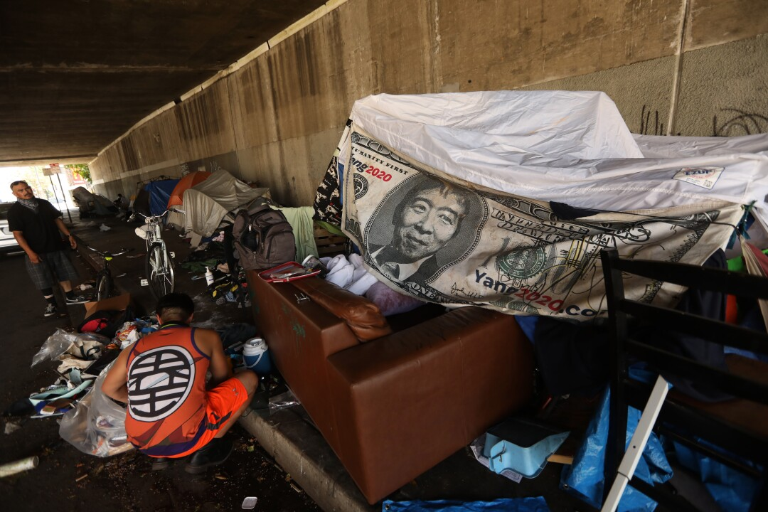 A banner depicting Andrew Yang on a $1,000 bill helps provide shelter in an encampment under the 134 Freeway.