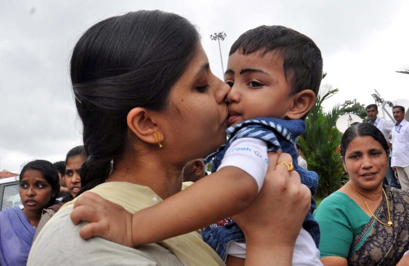 An Indian nurse, who was among 46 nurses stranded in territory held by Islamic extremists in Iraq, kisses her nephew upon arrival at the airport in Kochi, India, Saturday, July 5, 2014. The nurses who had been holed up for more than a week in Tikrit, returned home to southern India on Saturday aboard a special flight, officials said. (AP Photo/Satheesh)