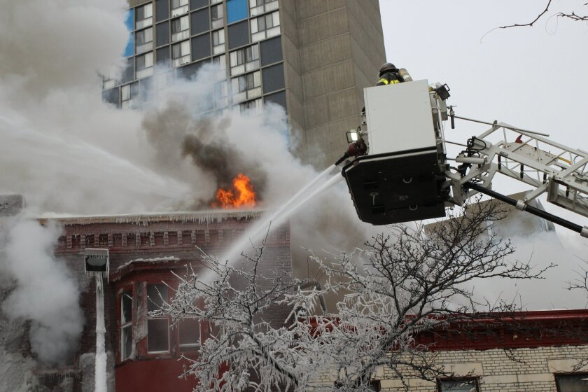 Crews battle a Minneapolis apartment fire on Wednesday, Jan. 1, 2014. The billowing fire engulfed a three-story building, sending 13 people to hospitals with injuries ranging from burns to trauma associated with falls. (AP Photo/Jeff Baenen)