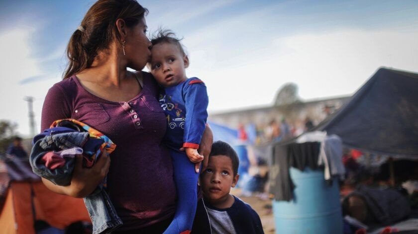 A Honduran mother stands with her sons at a temporary shelter for members of the migrant caravan Nov. 21 in Tijuana.