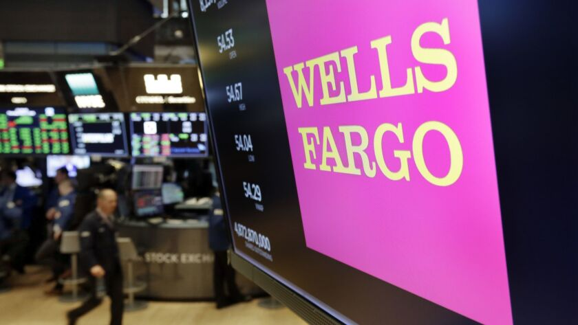 The logo for Wells Fargo appears above a trading post on the floor of the New York Stock Exchange, T