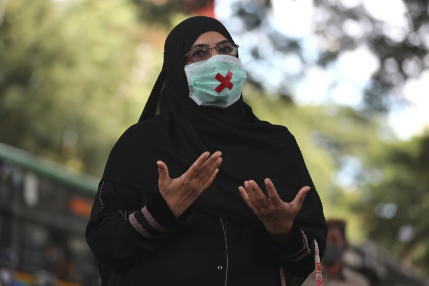 An Indian woman wearing a face mask as a precaution against the coronavirus speaks during a protest condemning the alleged gang rape and killing of a Dalit woman, in Bengaluru, India, Sunday, Oct. 4, 2020. India is the second worst-nation in terms of confirmed coronavirus caseload with 6.5 million cases. More than 100,000 people have died because of COVID-19. (AP Photo/Aijaz Rahi)