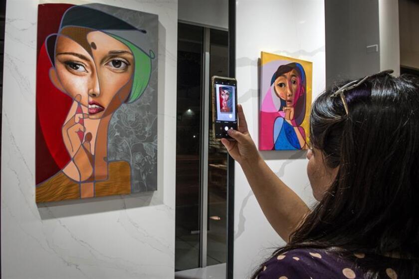 """Una mujer fotografía hoy una de las obras del artista español Miguel Ángel Belinchón que forma parte de la muestra """"Under Sanctorum"""", en la Galería Cosentino City Miami de Miami, Florida (EE.UU.). EFE"""
