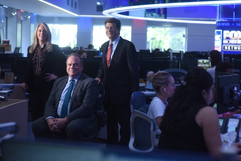 Chris Stirewalt, seated, is flanked by polling chief Dana Blanton and analyst Arnon Mishkin in the Fox News newsroom.