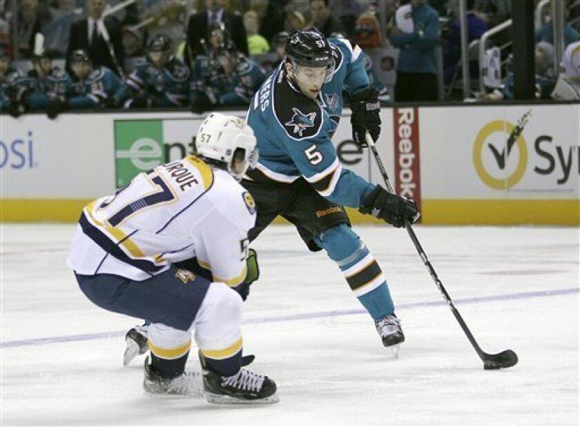 San Jose Sharks Jason Demers (5) skates past Nashville Predators left wing Gabriel Bourque (57) during the first period of an NHL hockey game in San Jose, Calif., on Saturday, Feb. 2, 2013. (AP Photo/Tony Avelar)