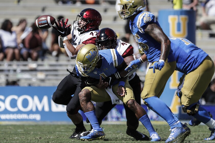 UCLA quarterback Dorian Thompson-Robinson passes under pressure from San Diego State rushers Kyahva Tezino and Keshawn Banks during second quarter action at the Rose Bowl on Saturday.