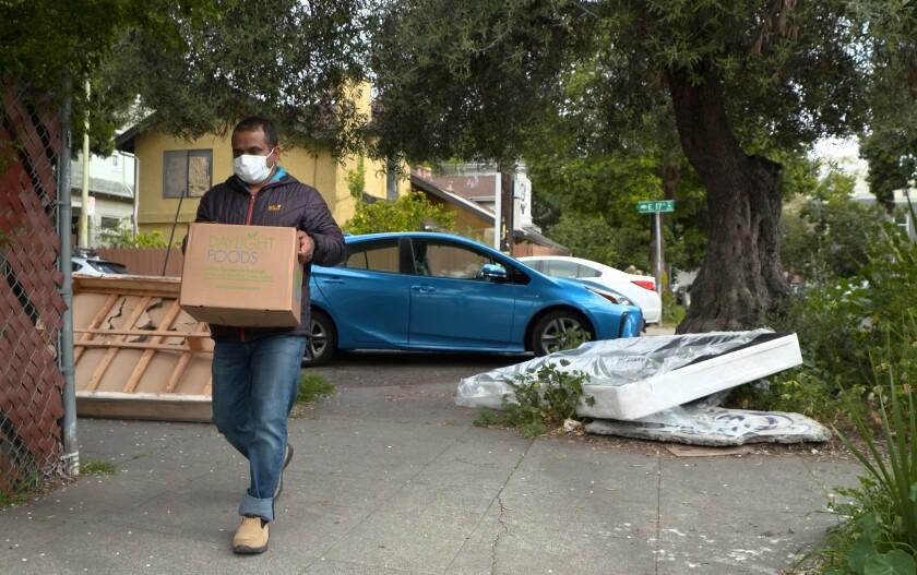 Prem Pariyar, in a mask, walks along a sidewalk carrying a cardboard box.