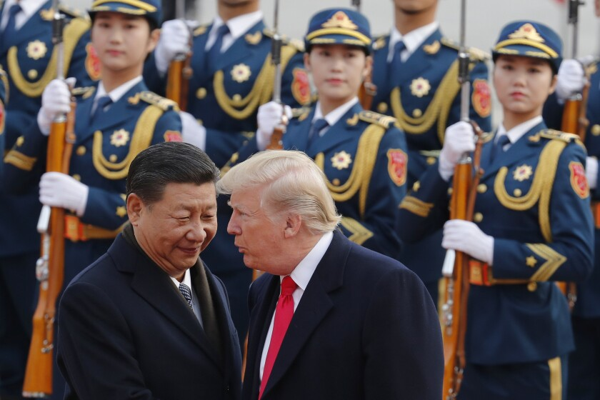 U.S. President Donald Trump, right, chats with Chinese President Xi Jinping during a welcome ceremony at the Great Hall of the People in Beijing in 2017. Some financial experts the U.S.-China trade dispute could drag into 2020.