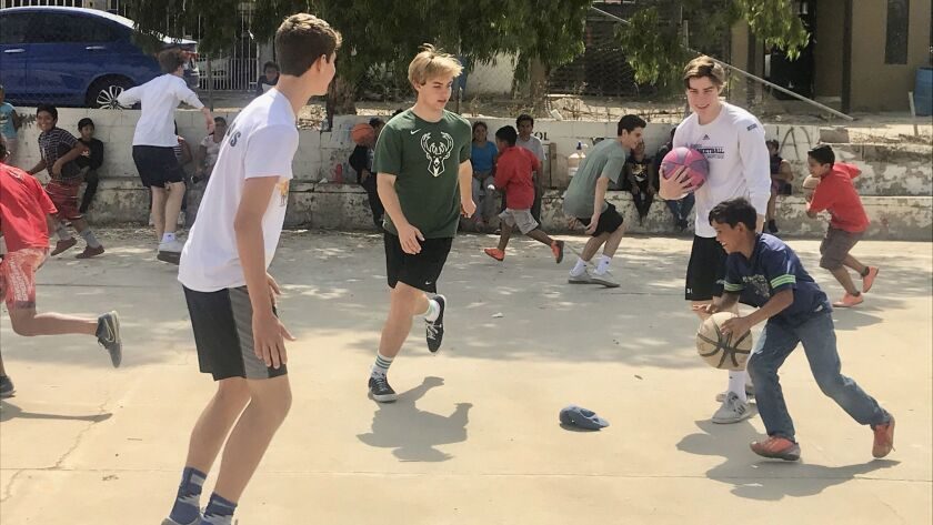 Pacific Ridge School junior Alex Nalbandian (center) is surrounded by teammates and a Mexican boy during a recent basketball clinic.
