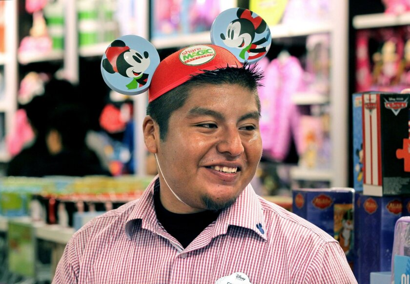 Enrique Guzman wears Mickey Mouse ears while he works as a seasonal employee at the Disney Store at Carlsbad Premium Outlets.