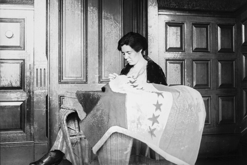 In this photo from the 1920s, Alice Paul sews a suffrage flag in Washington.