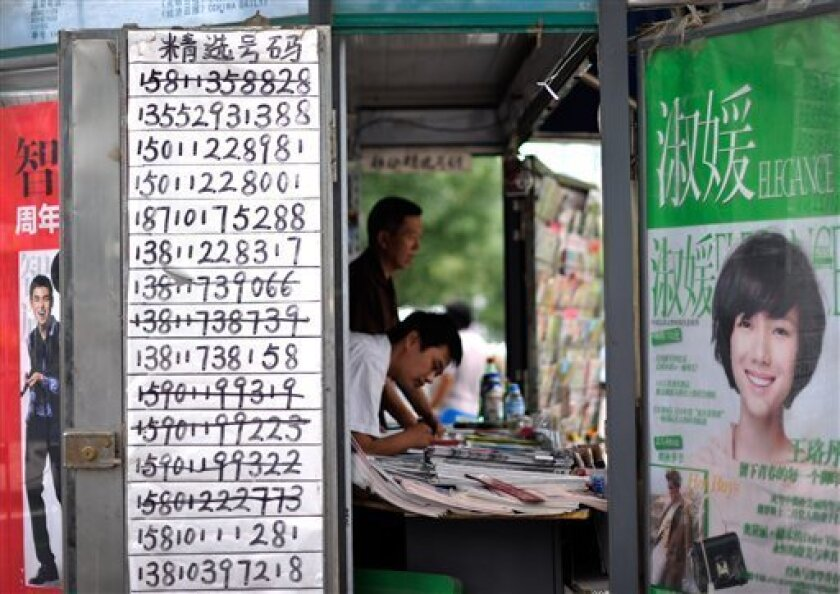 A vendor browses magazine at a news stand with a paper displaying mobile phone numbers for sale in Beijing, Wednesday, Sept. 1, 2010. China began requiring identification on Wednesday from anyone purchasing a new mobile phone number in what it says is a bid to stamp out rampant junk messages but that some say is raising new privacy concerns. (AP Photo/Andy Wong)